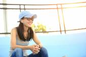 Woman skateboarder sit on skatepark stairs listening music from smart phone mp3 player — Stock Photo