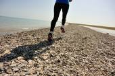 Runner athlete running on stone beach of qinghai lake. — 图库照片