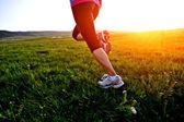 Runner athlete legs running on grass seaside — ストック写真