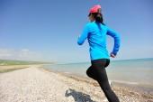 Runner athlete running on stone beach of qinghai lake — Stock Photo
