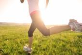 Runner athlete legs running on grass seaside. — Stock Photo