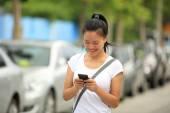 Mujer usar su teléfono celular caminando en el estacionamiento — Foto de Stock