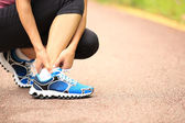 Woman runner hold her twisted ankle — Stock Photo