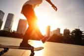 Woman skateboarder skateboarding at sunrise city — ストック写真