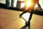 Woman skateboarder skateboarding at sunrise city — Stock Photo