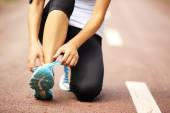 Jonge vrouw loper koppelverkoop schoenveters — Stockfoto