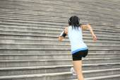 Runner athlete running on stairs. listening to music in headphones from smart phone mp3 player smart phone armband. — Stock Photo
