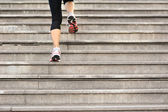 Sports woman legs running up on stone stairs — Photo