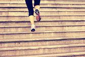 Sports woman legs running up on stone stairs — Zdjęcie stockowe
