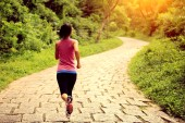 Young fitness woman running at forest trail — Stock Photo