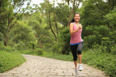 Young fitness woman running at forest trail — 图库照片