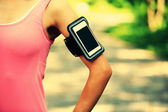 Runner athlete listening to music from smart phone mp3 player smart phone armband. — Stock Photo