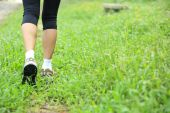Running hiking legs on green grass — Zdjęcie stockowe