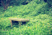 Stone bench in forest grass — Zdjęcie stockowe
