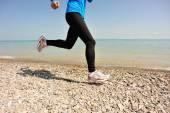 Runner athlete running on stone beach of qinghai lake. — Zdjęcie stockowe