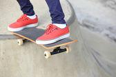 Young woman legs skateboarding at skatepark ramp — Stock Photo