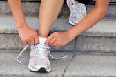 Young woman runner tying shoelaces — Stock Photo