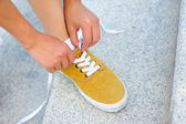 Woman skateboarder tying shoelace — Stock Photo