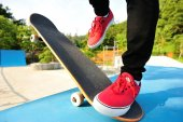 Skateboarding woman legs at skatepark — Stock Photo