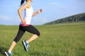 Runner athlete running on grass seaside. woman fitness jogging workout wellness concept. — Stock Photo