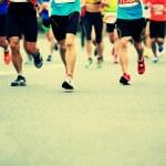 Unidentified marathon athletes legs running on city road — Stock Photo #59976915
