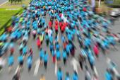 Unidentified marathon athletes legs running on city road — Stock Photo