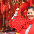 Young asian woman with red chinese knot wishing you a happy chinese new year — Stock Photo #60617509