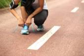Female tying shoelaces — Foto de Stock