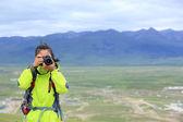Woman holding  taking photo at plateau — Stock Photo