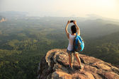 Hiker on mountain top with smartphone — Stock Photo