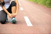 Woman runner tying shoelace — Zdjęcie stockowe