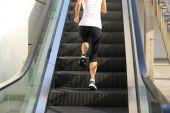 Woman running on escalator stairs — Stock Photo