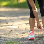 Постер, плакат: Woman runner tying shoelaces