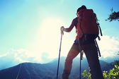 Woman backpacker on mountain peak — Stock Photo