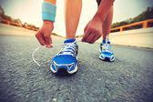 Vrouwelijke atleet gelijkmakende schoenveter — Stockfoto