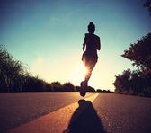 Young fitness woman running on sunrise — Stock Photo