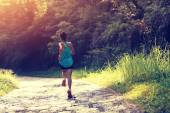 Female athlete running on forest trail. — Stock Photo