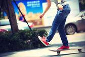 Young skateboarder legs on skateboard — Stock Photo