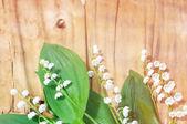 Piękny konwalie na drewniane tło — Zdjęcie stockowe