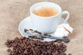 Delicious freshly brewed cup of coffee with whole beans on burla — Stock Photo