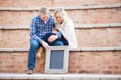 Happy young adult couple looking down at your text, focus on sig — Stock Photo
