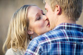 Young adult couple kissing outside in daytime — Stock Photo