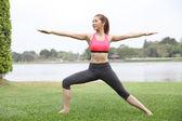 Yoga virabhadrasana II warrior pose by woman on lawn,left side — Stock Photo