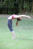 Yoga Ardha Chandrasana (back bend) pose by woman on lawn — Stockfoto