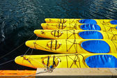 Yellow canoes, kayaks , 5 pieces, are on the water, attached to the shore, shrouded , tied a rope to the castle , around the water shine — Stock Photo