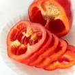 Постер, плакат: Red bell pepper lies on a white plate on a white background ele