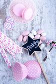 Sugar coated candies, cupcake baking cups, macaroons, pink straws — Stock Photo