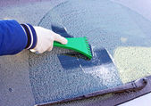 Cleaning frozen car window from the ice — Stock Photo