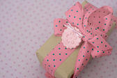 Pink and white polka dot gift box with ribbon and bow — Stock Photo