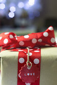 Rustic Gift with red bow and Christmas lights — Stock Photo